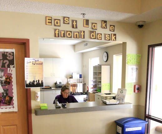 A student works at the East Lake front desk, ready to welcome.
