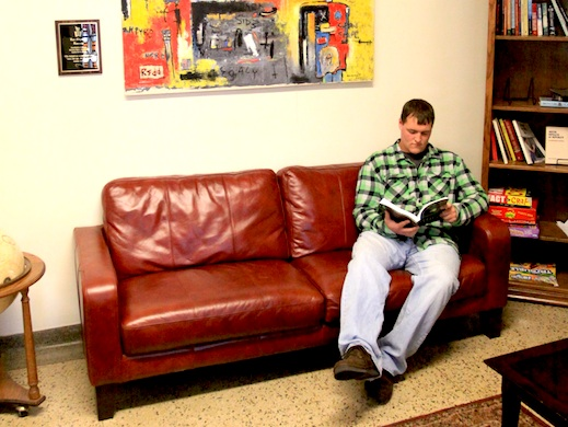 A student reads in a hall lounge.