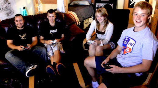 Students play video games together in a dorm room.