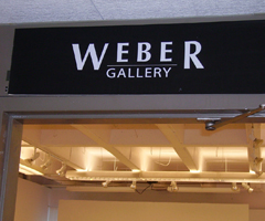 The Weber Gallery sign, white crisp words against a black background welcomes the viewer into the well-lit, intimate gallery.