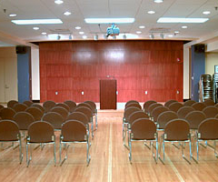The Art Tye Lounge is a well lit area featuring a podium and audience seating.