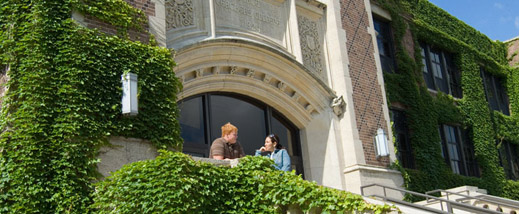 Two students talk next to a vine covered wall by Somsen Hall's main entrance